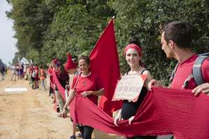"""Greenpeace activists join the protest against brown coal mining at Hambach near Cologne. They create a human chain with red textile banner -  as part of a protest series - the climate camp at the lignite mining ground  belonging to the energy concern RWE. They set a red line against the exploration and usage of fossil fuel energy. The banners read: """"Future instead of lignite!"""" and """"Save the climate. Stop Coal!"""" Greenpeace Aktivisten beteiligen sich an der Menschenkette """"Rote Linie gegen Kohle"""" am Hambacher Tagebau. Sie protestieren  gegen die fortgesetzte Foerderung von Braunkohle durch den Energiekonzern RWE."""